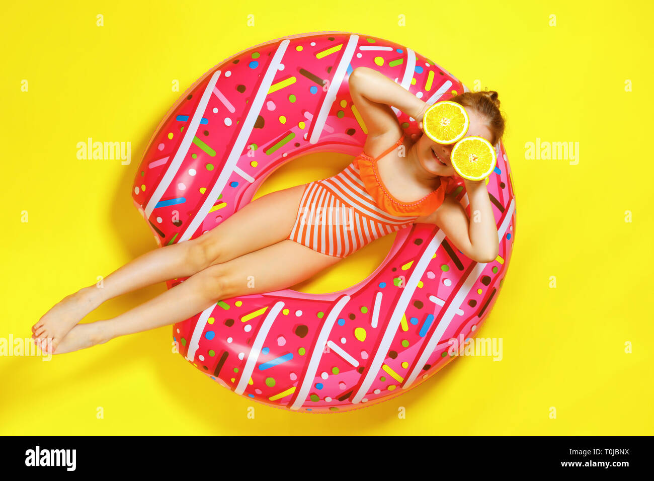 A little child girl in a swimwear suit lying on a donut inflatable circle. Yellow background. Top view. Summer concept. - Stock Image