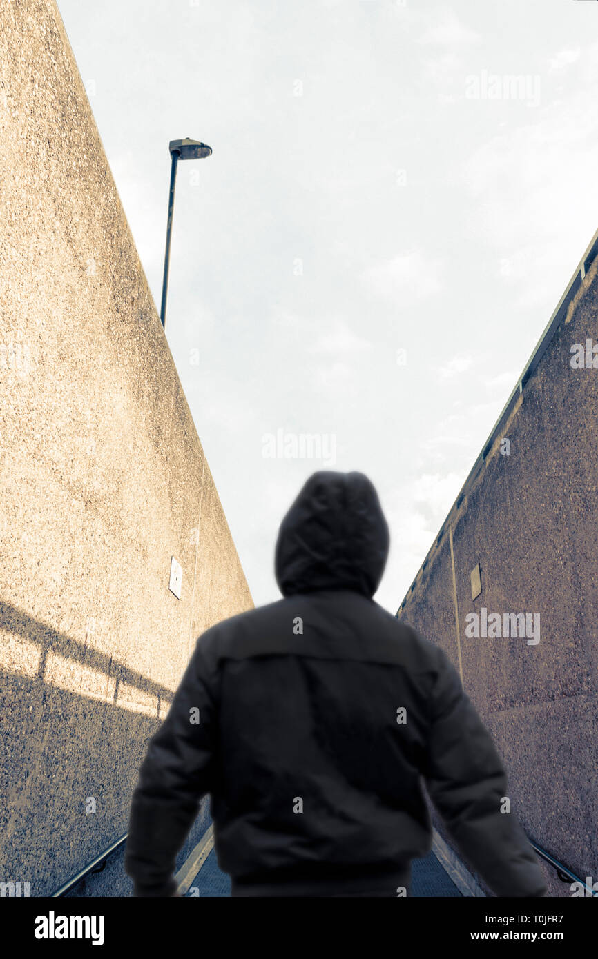 Rear view of a silhouetted figure in a hoodie, back to camera, emerging from an underpass and walking away on an upward slope Stock Photo