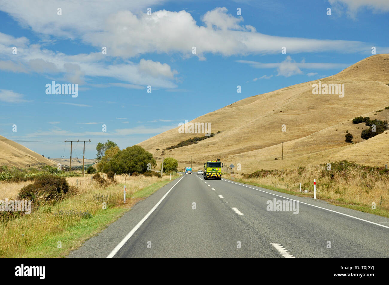 State Highway 1 in the Marlborough region of the South Island of New Zealand. SH1. Road traffic driving through rolling hills countryside in summer - Stock Image