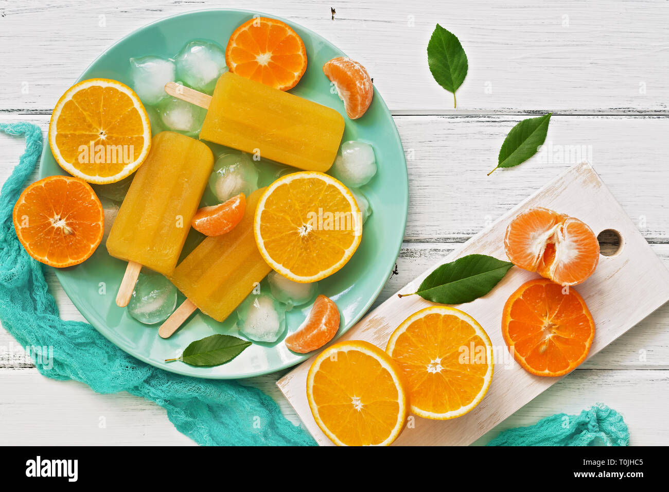 Popsicle orange with slices of fresh orange, mandarin and green leaves on a white rustic plank table. Top view, flat lay. Stock Photo