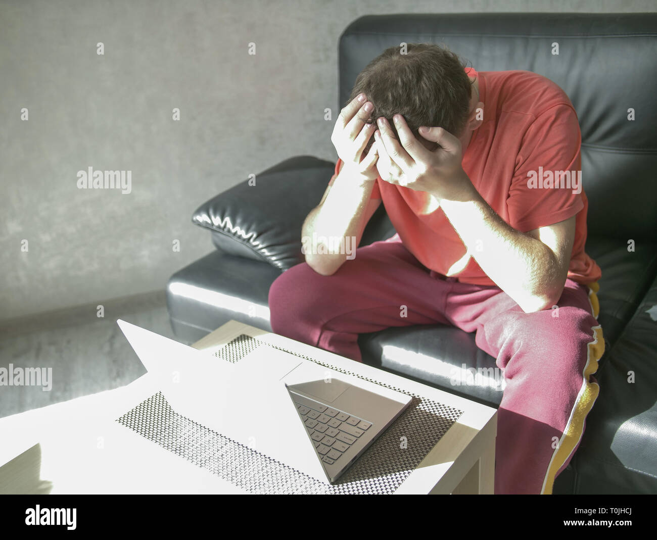Young man sits near a laptop in her living room, copyspace - Stock Image