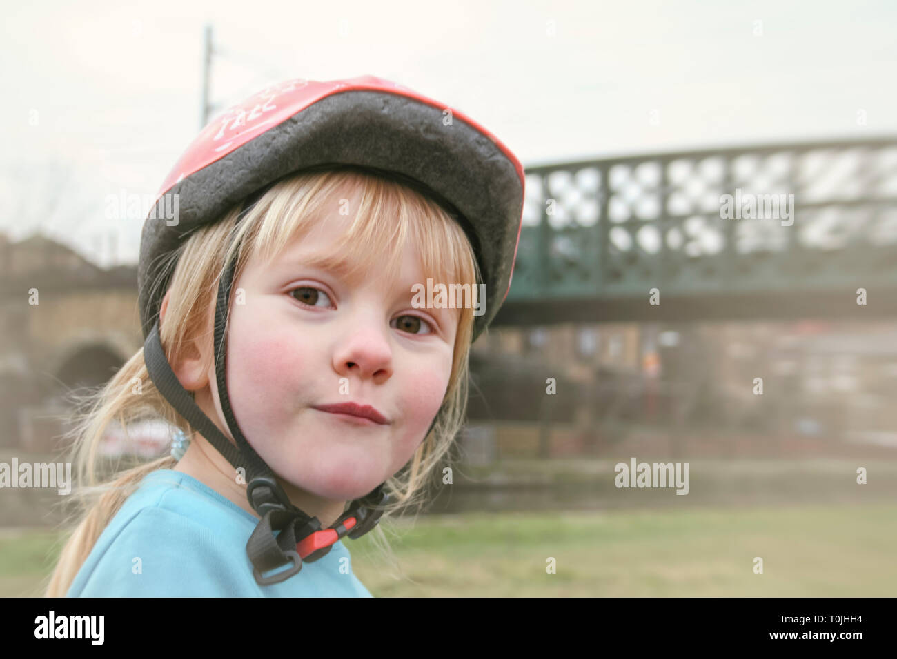 Close-up portrait of cute 6-year old girl wearing a cycling helmet, looking at camera - Stock Image