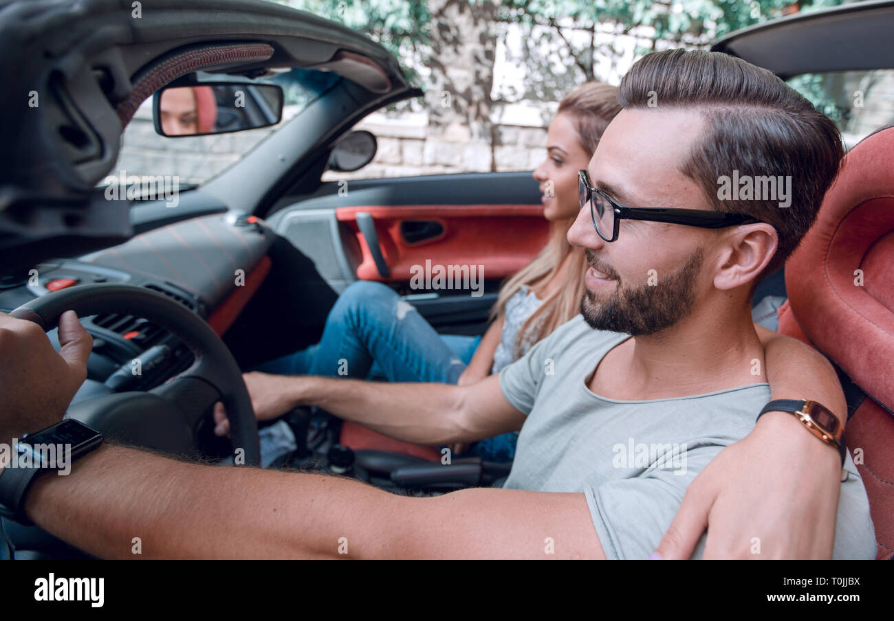 Happy couple inside convertible car in day trip - Stock Image