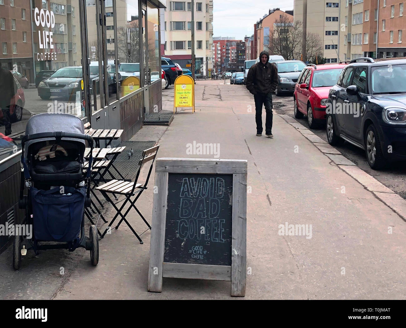 20 March 2019, Finland, Helsinki: A pram stands in front of Good Life  Coffee Cafe next to a sign with the inscription 'Avoid Bad Coffee'. The quality of life in the far north ensures that the World Happiness Report is not just about the Finns, but also about other Scandinavians. (to dpa 'Report: In Finland people are still happiest') Photo: Steffen Trumpf/dpa - Stock Image