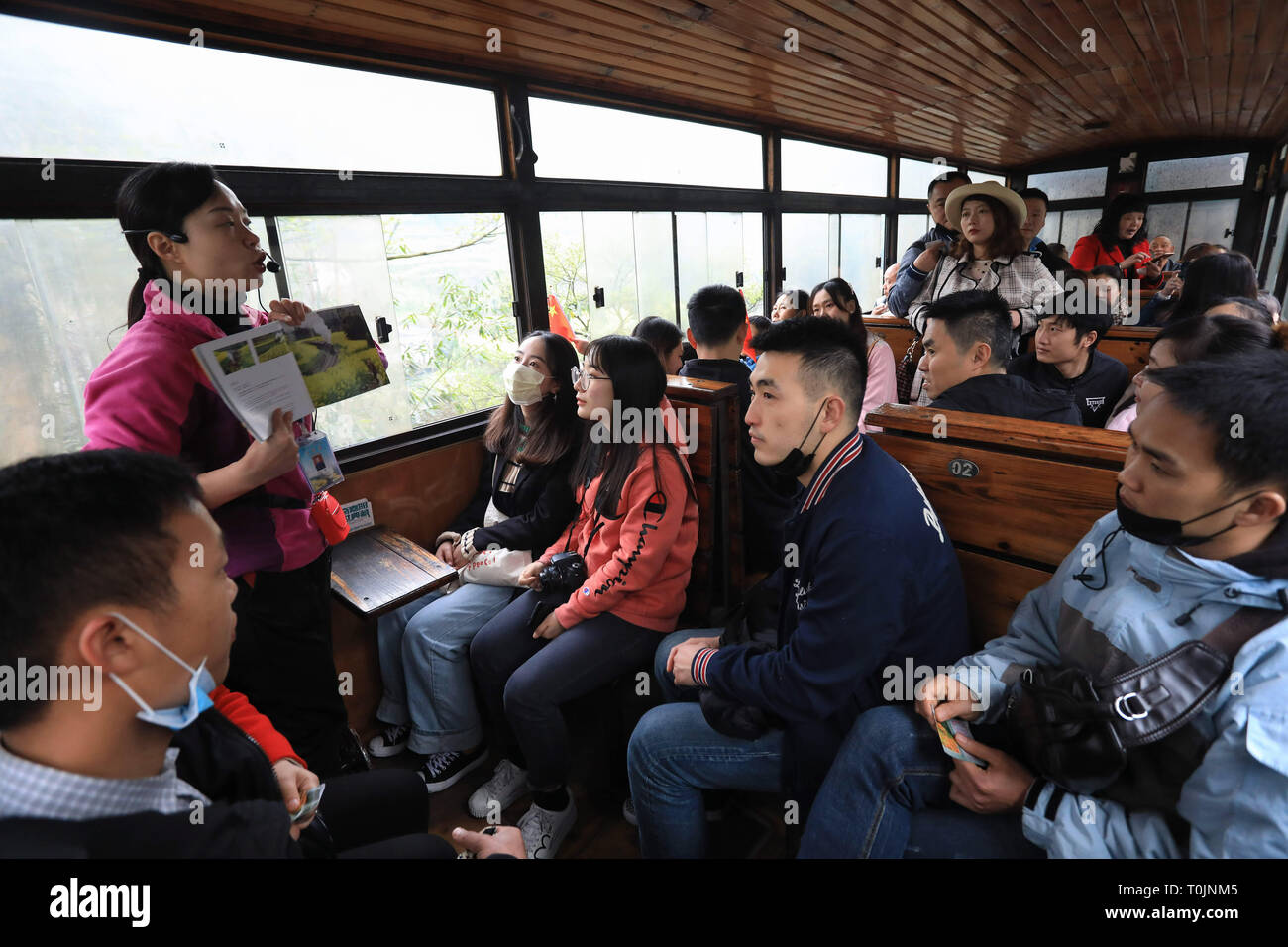 Qianwei, China's Sichuan Province. 20th Mar, 2019. Tourists listen as a guide explains in a Jiayang steam train running on a narrow gauge railway in Qianwei County, southwest China's Sichuan Province, March 20, 2019. The old-fashioned steam train, running on a narrow gauge railway in Qianwei County, serves mainly in sightseeing, but as increasing number of tourists visit the county in recent years, the train itself has become an attraction providing a journey of reminiscence. Credit: Jiang Hongjing/Xinhua/Alamy Live News - Stock Image