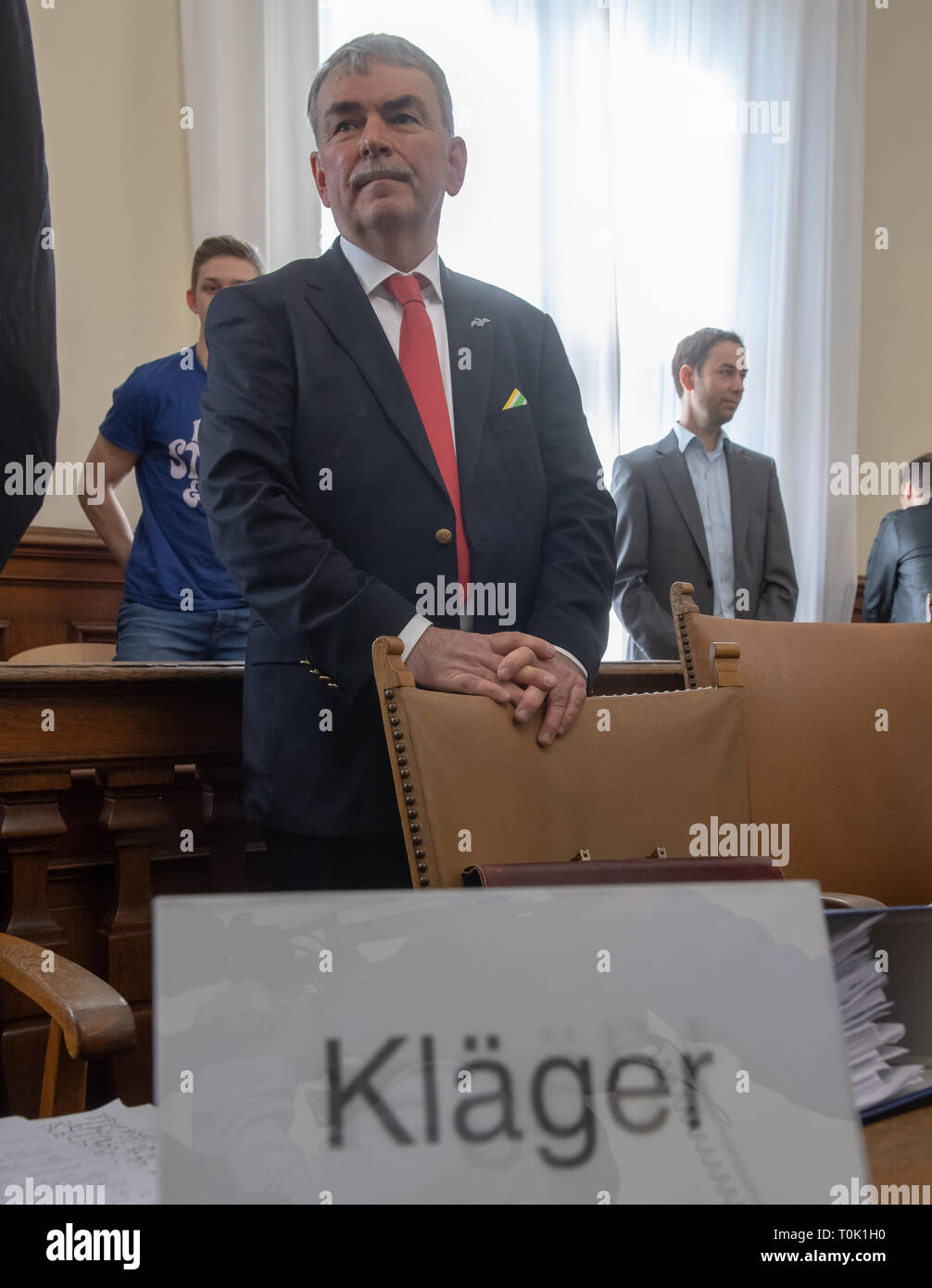 20 March 2019, Bavaria, München: The plaintiff Gustl Mollath stands in his place in the courtroom. In the trial, Mollath demands about 1.8 million euros from the Free State of Bavaria for his unjustified placement in a psychiatric institution. Photo: Peter Kneffel/dpa - Stock Image