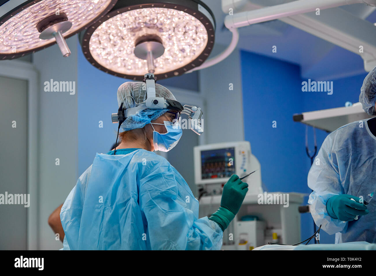surgery, medicine and people concept - group of surgeons at operation in operating room at hospital - Stock Image