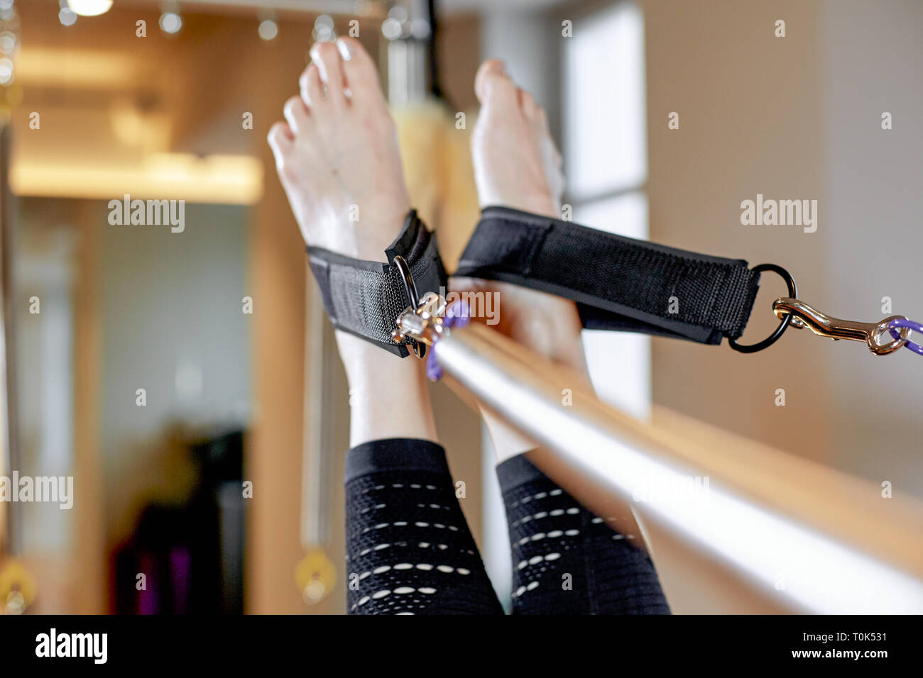 gym woman pilates stretching sport in reformer bed instructor girl. Legs close up - Stock Image