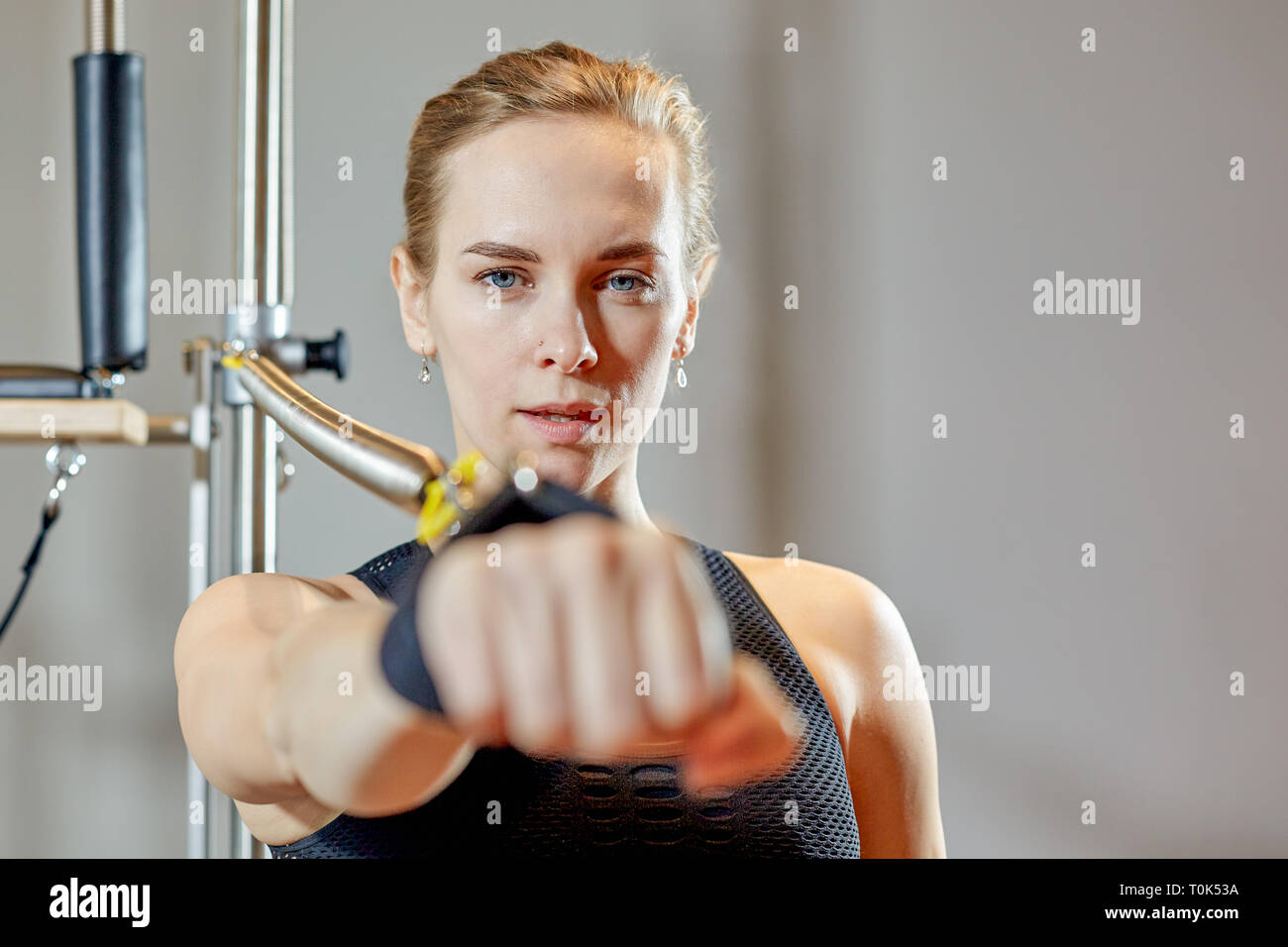 gym woman pilates stretching sport in reformer bed instructor girl. Healthy Smiling Woman Wearing Leotard Practicing Pilates. Selective focus - Stock Image