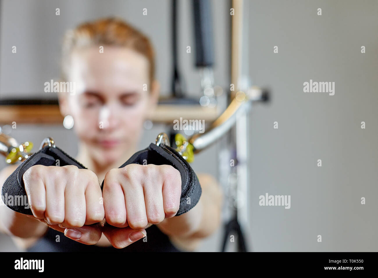 gym woman pilates stretching sport in reformer bed instructor girl. Selective focus on hands - Stock Image