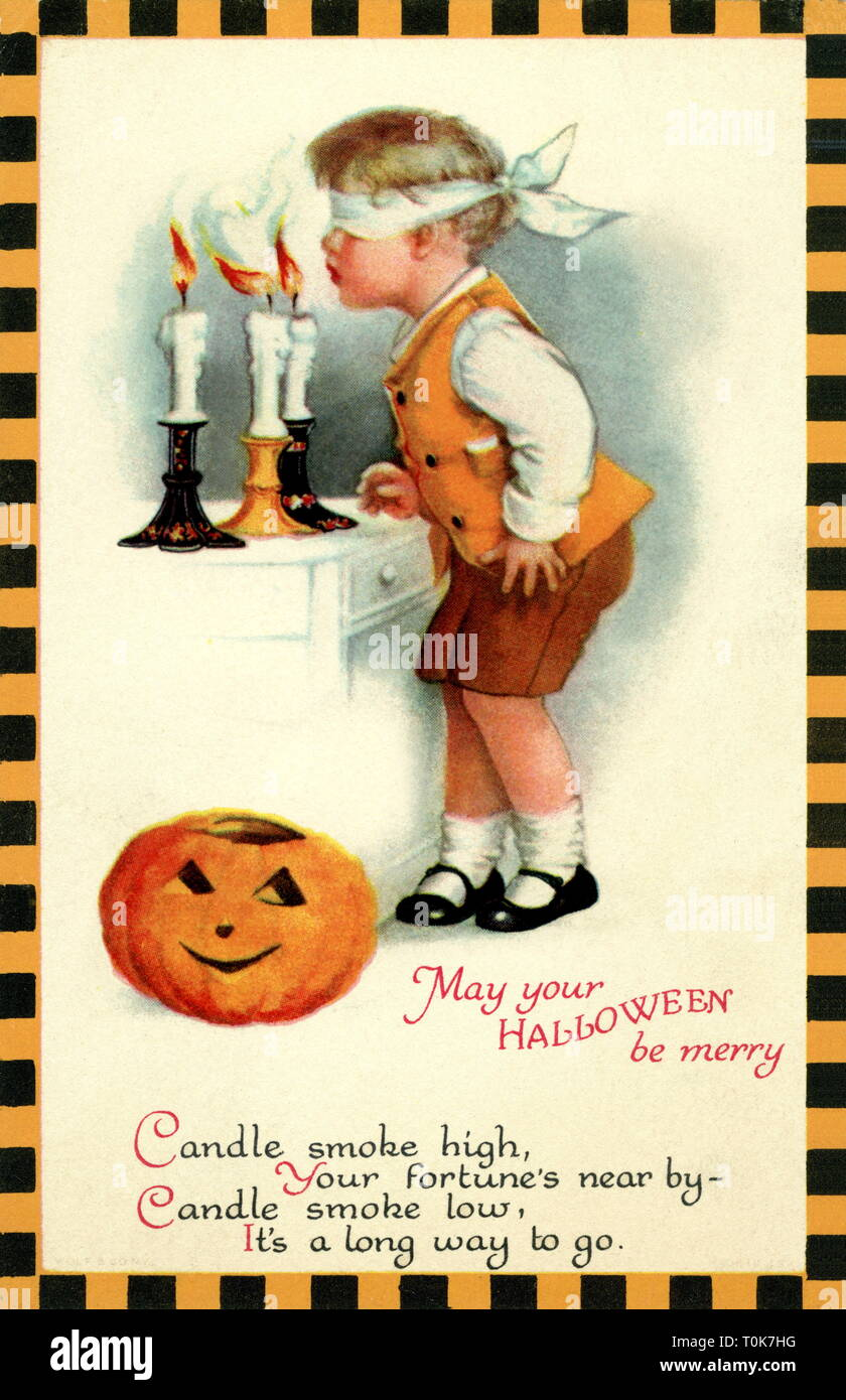 festivities, Halloween, boy with blindfolded eyes blowing out candles, depending on, how the candles smoke is blowing, he will get soon lucky or not, postcard, USA, circa 1927, Additional-Rights-Clearance-Info-Not-Available - Stock Image