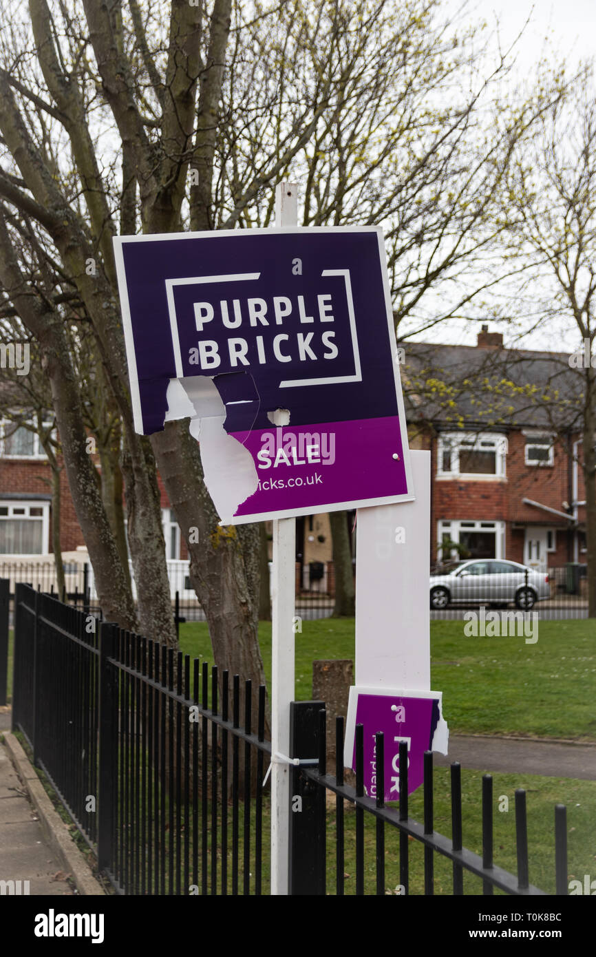 Ripped and broken Purple bricks estate agents for sale or sold sign - Stock Image