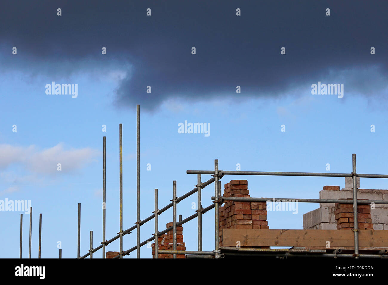 Storm clouds gathering over a building site with scaffolding and bricks piled up - Stock Image