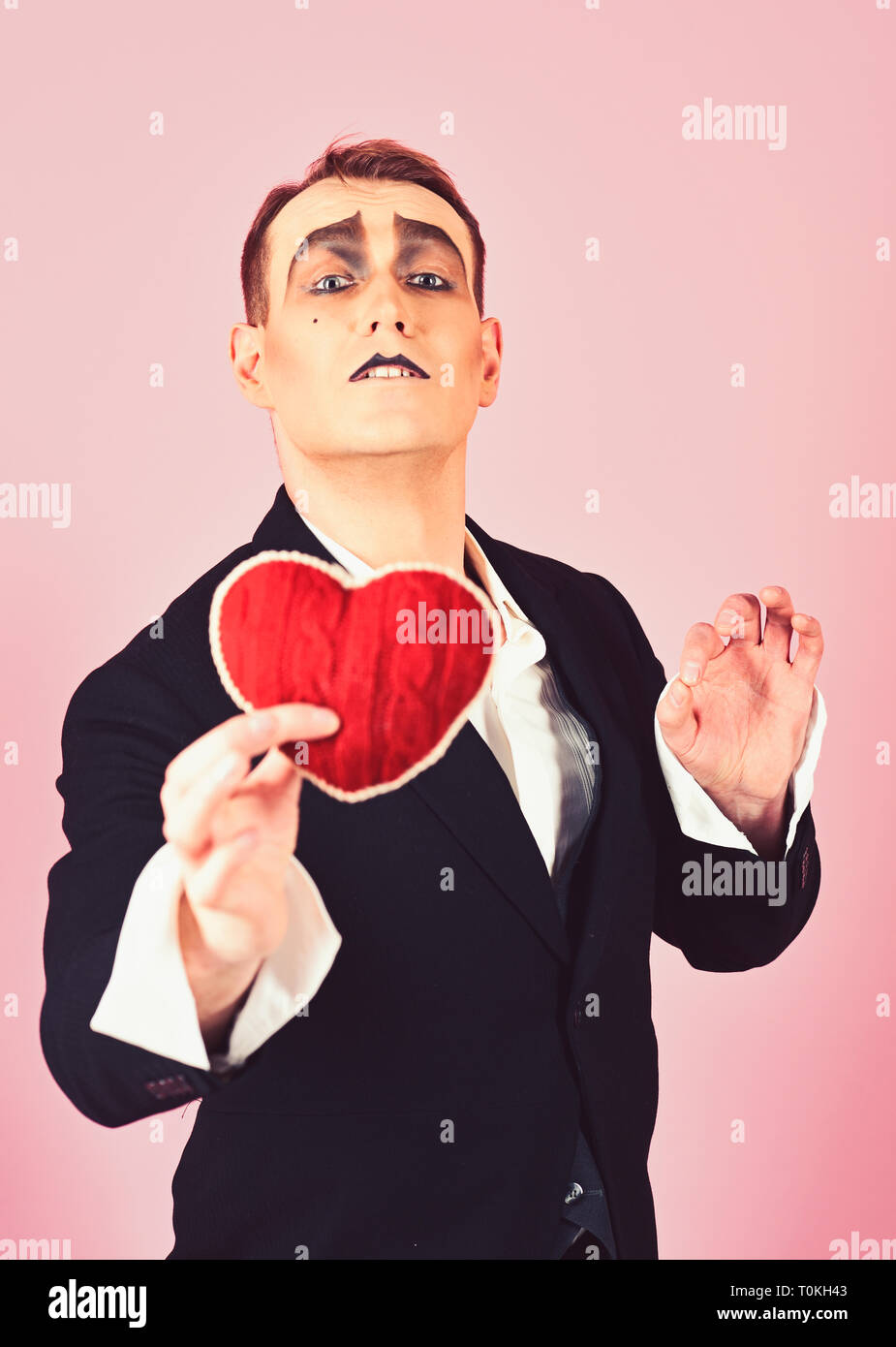Serious about someone. Love confession on valentines day. Mime man hold red heart for valentines day. Mime actor with love symbol. Theatre actor - Stock Image
