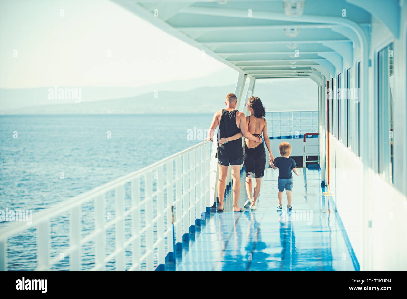 family with son walking on cruise liner deck, full body. - Stock Image