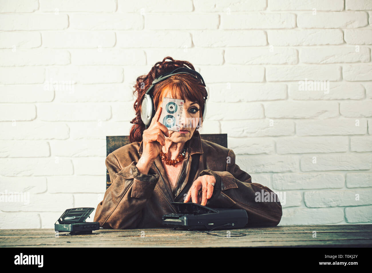 Old woman with cassette recorder listen music in headphones. - Stock Image