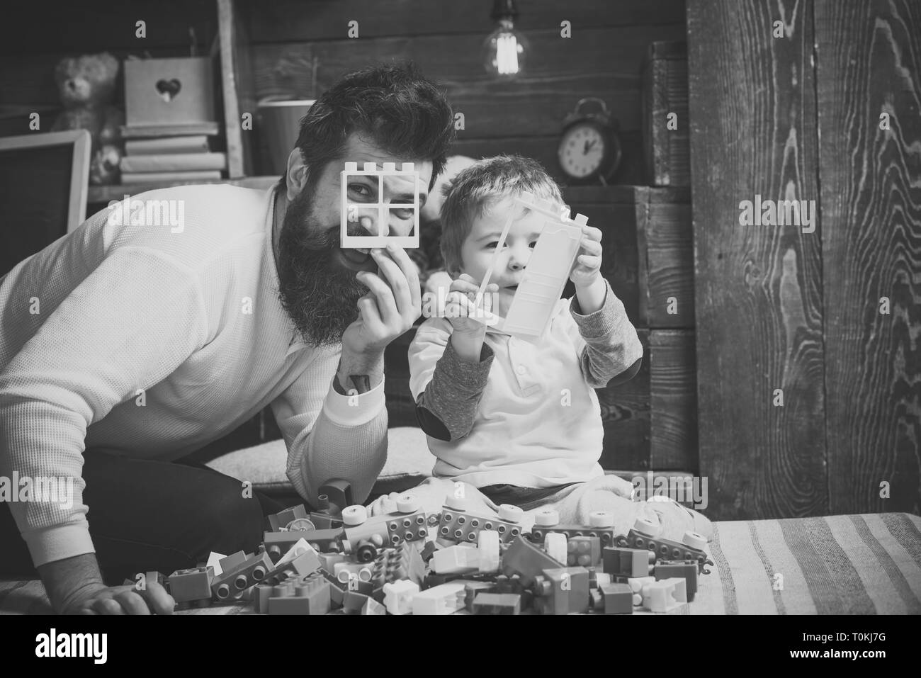 Father and son play with constructor. Fatherhood concept. Family play with constructor at home. Dad and child play with details of constructor - Stock Image