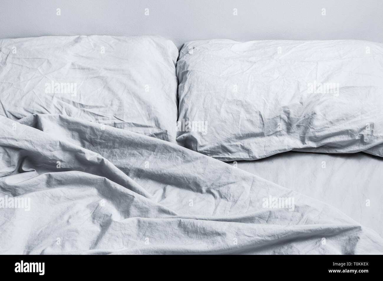 Messy gray bed linen. Bed with two pillows in daylight. - Stock Image