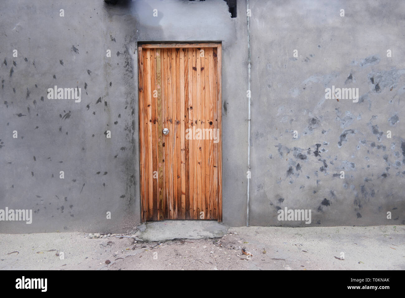 Wooden door and old gray wall - Stock Image