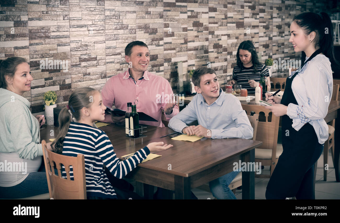 Parents with children are giving order to cheerful waitress in comfy cafe. - Stock Image