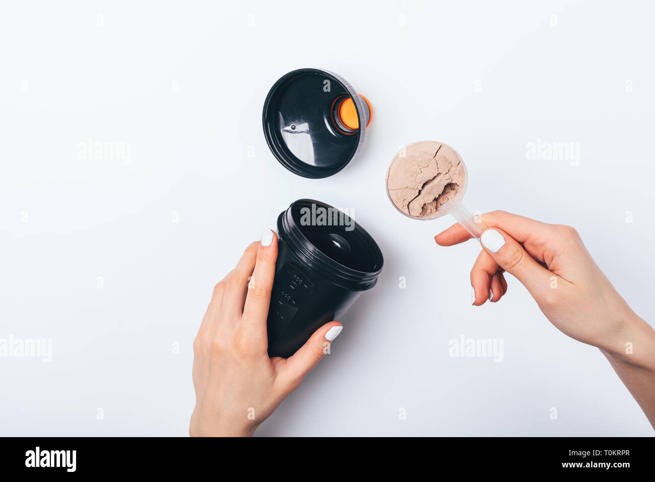 Woman's hands putting scoop of chocolate protein powder into black plastic shaker to prepare sports drink for muscle growth, top view on white table. Stock Photo