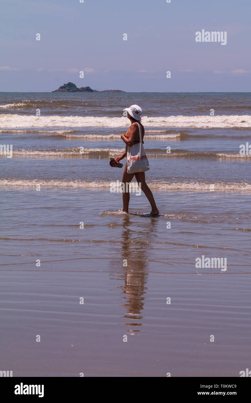 Middle-aged woman walking on the beach in Peruíbe SP Brazil - Stock Image