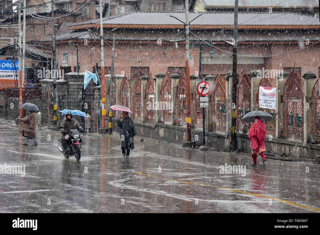 Kashmiri residents are seen walking amidst fresh snowfall during a shut-down in Srinagar. Lives were affected in Kashmir valley on Wednesday due to a protest shutdown called by the separatists against the custodial death of a school teacher yesterday. Forces in adequate numbers were also deployed in sensitive areas to thwart any protests in view of shutdown call issued by the seperatists. - Stock Image