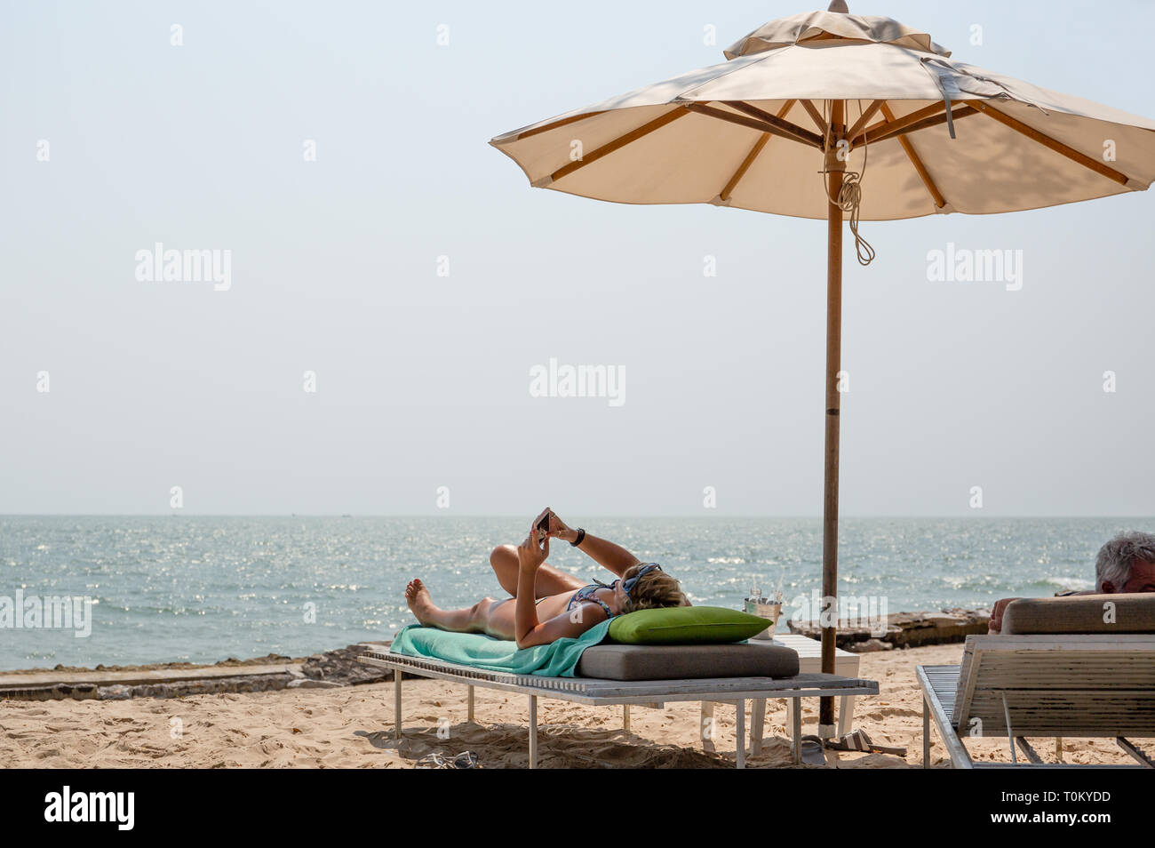 Retried couple lying on deckchairs using cell phone on the beach. - Stock Image