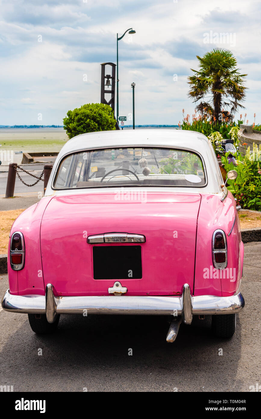 A classic pink oldtimer car parked on the coast in Cancale, Brittany, France Stock Photo