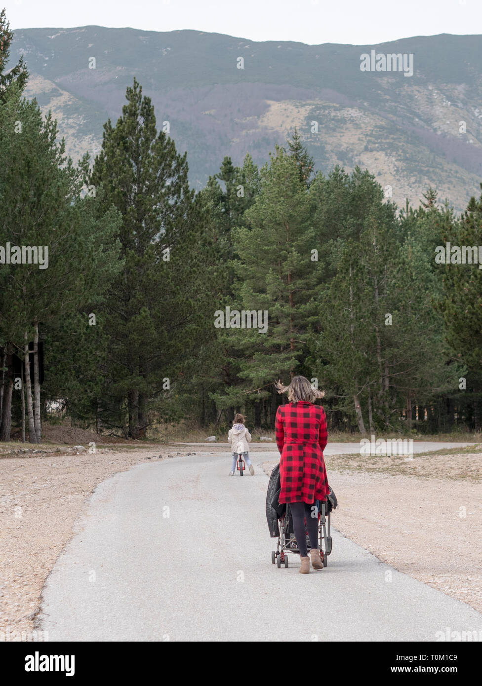 Mom walking with stroller and small kid on bicycle on mountain road from the back - Stock Image