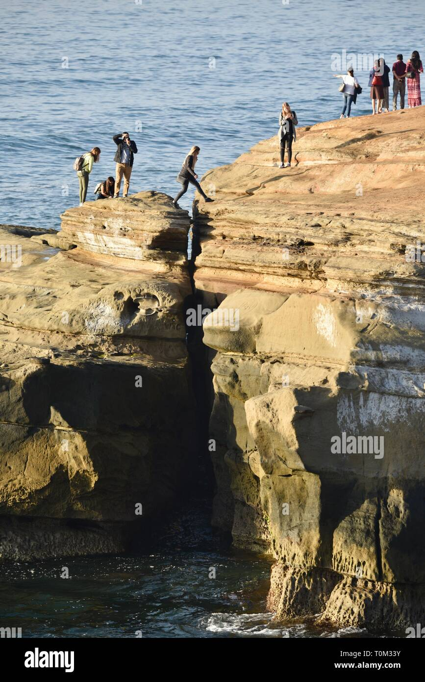 People exploring and jumping over rocky crevice on the sandstone cliffs of Sunset Cliffs, waves from Pacific Ocean, San Diego, CA, USA Stock Photo