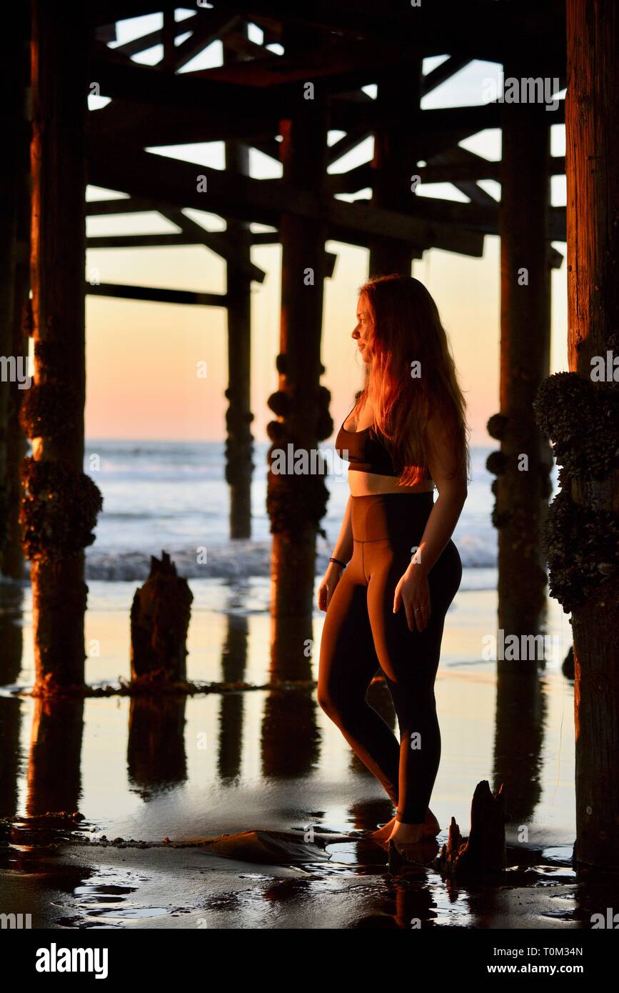 Attractive young woman in yoga pants standing under Crystal Pier watching sunset as tide slowly comes in, Pacific Beach, San Diego, CA, USA - Stock Image
