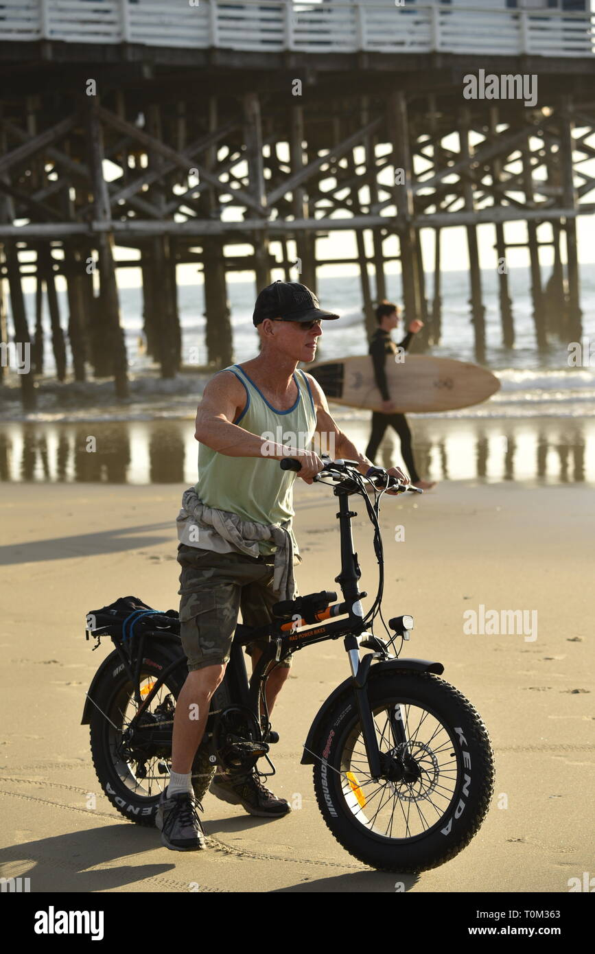 Fit, middle-aged man riding fat tire bicycle biking on beach during sunset at Pacific Beach, San Diego, California, USA Stock Photo