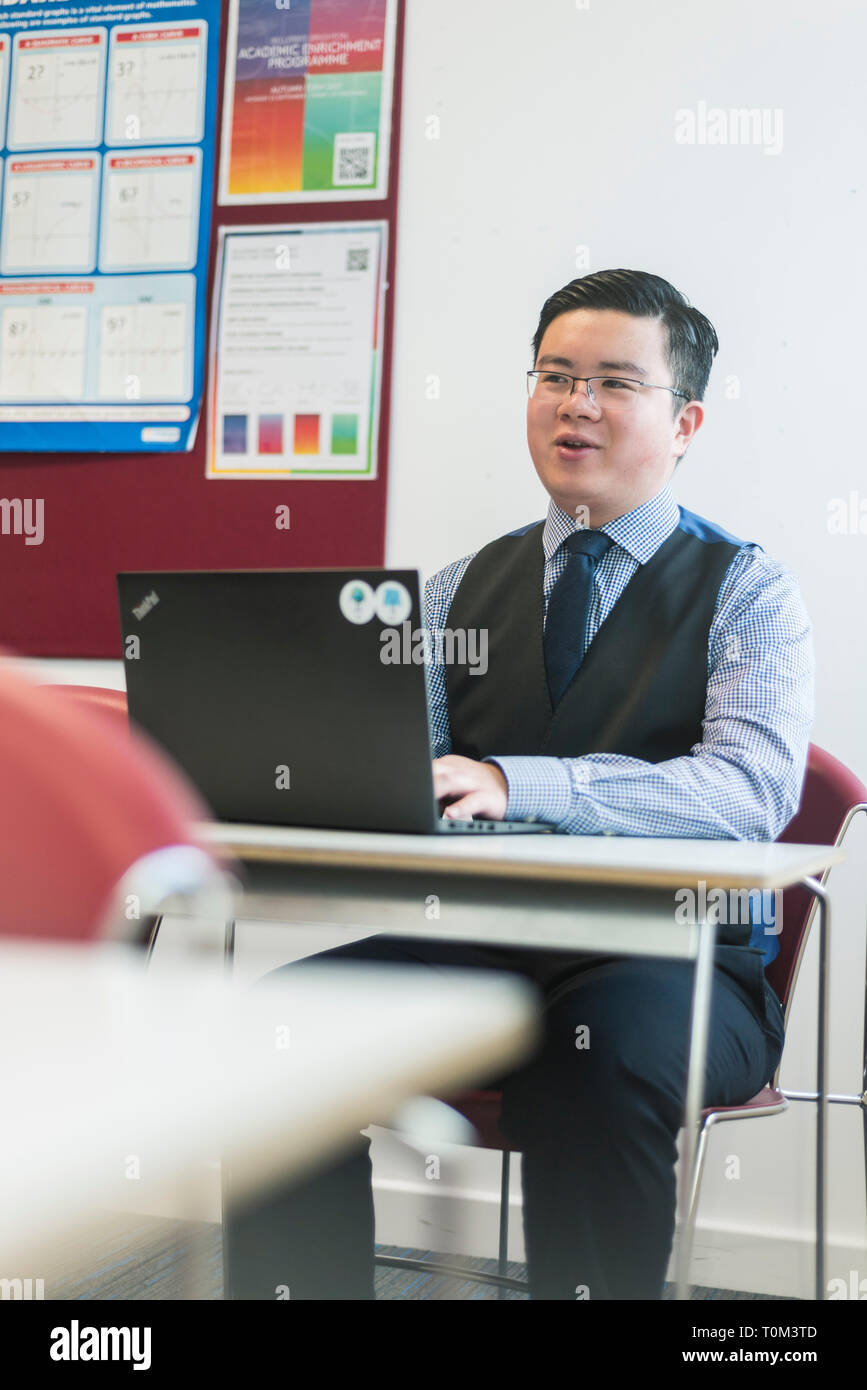 An international asian young male student sits in a classroom at a desk working and studying on his laptop in a modern classroom. Stock Photo