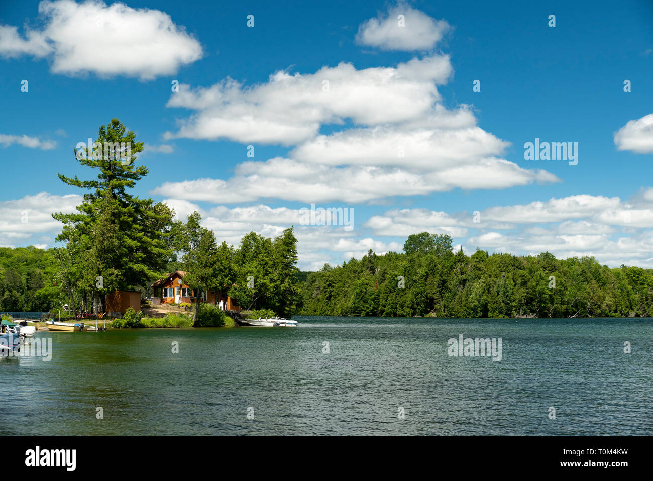 Cabin and docked motorboats on a lake in Ontario Canada's Cottage Country with clouds in a blue sky on a summer afternoon. Stock Photo