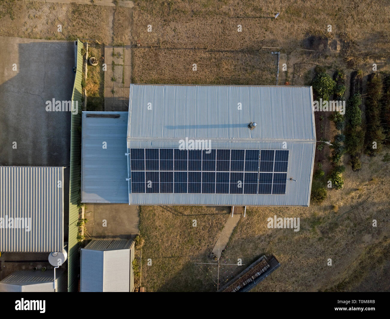 Solar panels roof aerial view in an Australian backyard with other sheds nearby. Victoria, Australia. - Stock Image