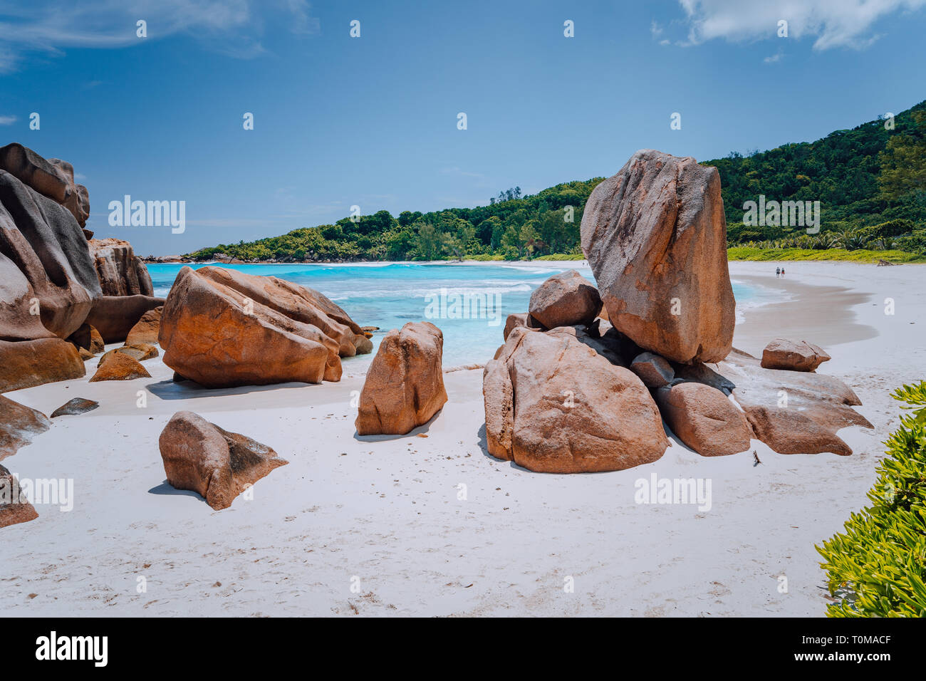 Couple on tropical beach lagoon with granite boulders in the turquoise water and a pristine white sand at Anse Cocos, La Digue island, Seychelles Stock Photo