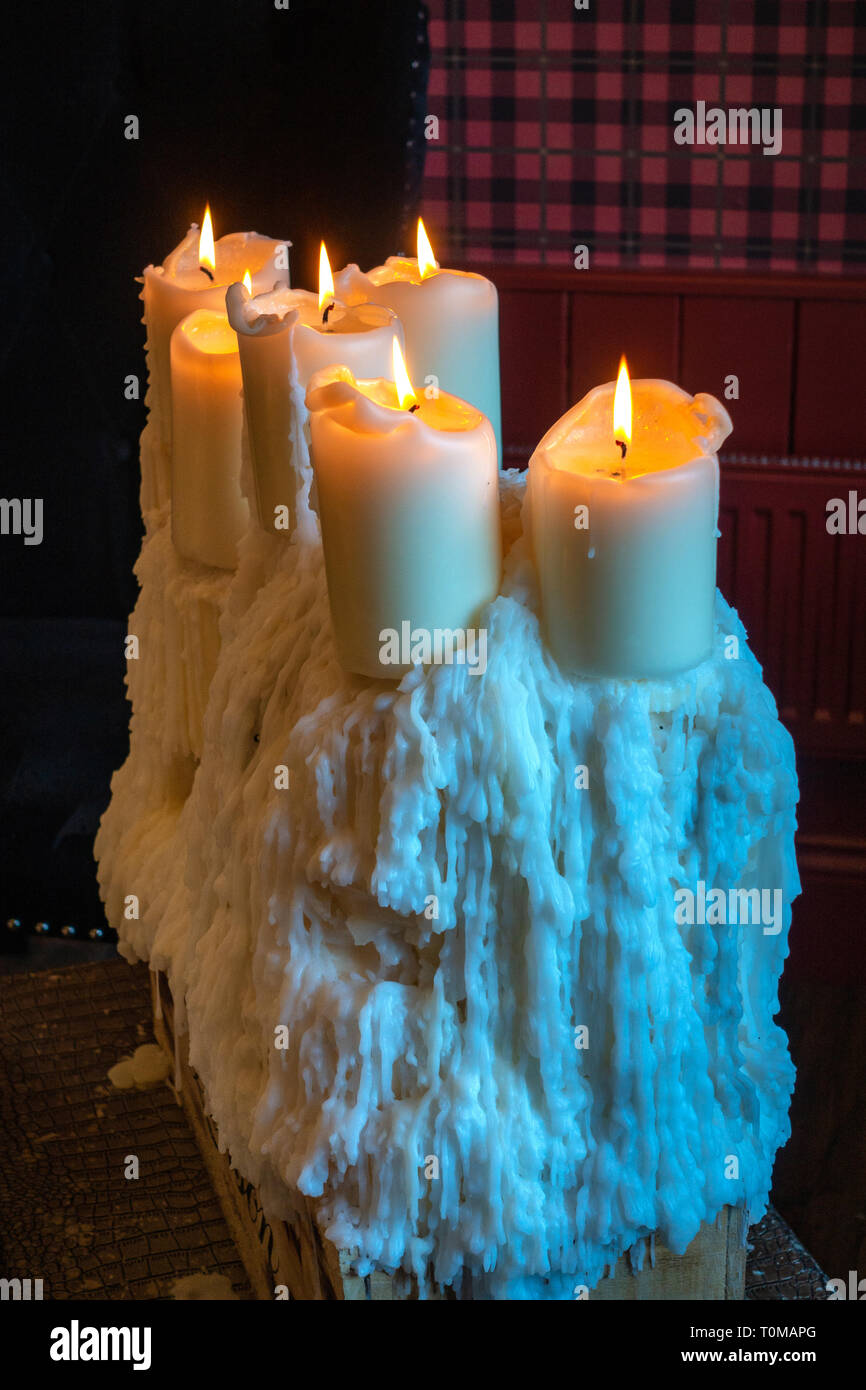 wonderful cluster of beautiful old church style candles perched on the top of a very large pile of old melted candle wax drippings - Stock Image