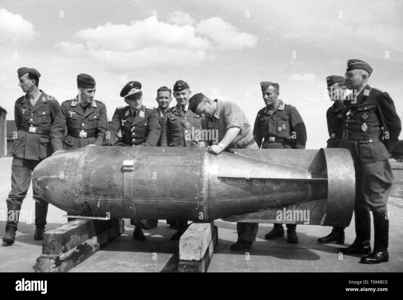 Second World War / WWII, aerial warfare, officers and non-commissioned officers of the German Luftwaffe (German Air Force) watching the work on an aircraft bomb, circa 1941, Additional-Rights-Clearance-Info-Not-Available - Stock Image