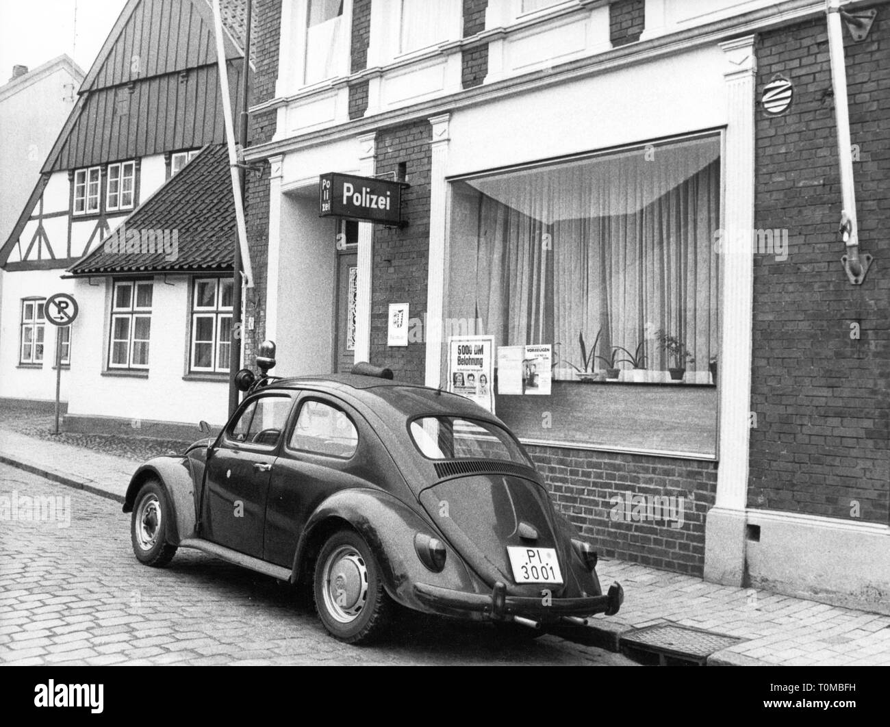 police, Germany, equipment, vehicles, VW Beetle 1300, version 1966, in front of the police station in Barnstedt, Schleswig-Holstein, 1971, Volkswagen, police station, state police, number plate, registration plate, license plate, number plates, registration plates, license plates, vehicle registration mark, Pinneberg, shop window, shop windows, building, buildings, exterior view, street, streets, parking, warrant of apprehension, description, warrants of apprehension, Wanted!, bill, placard, bills, posters, placards, wanted poster, passenger moto, Additional-Rights-Clearance-Info-Not-Available - Stock Image