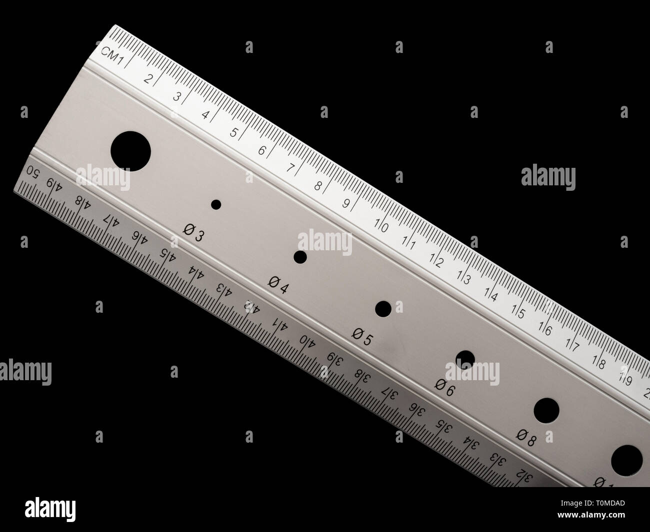 Cut-out of a linear ruler. Black background. Technical concepts. - Stock Image