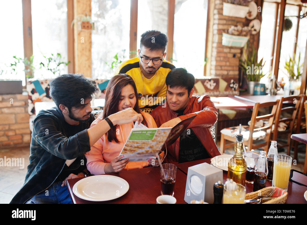Group Of Asian Friends Sitting Cafe Happy Indian People Having Fun Together Sitting On Couch And Choose Meals From The Menu Stock Photo Alamy