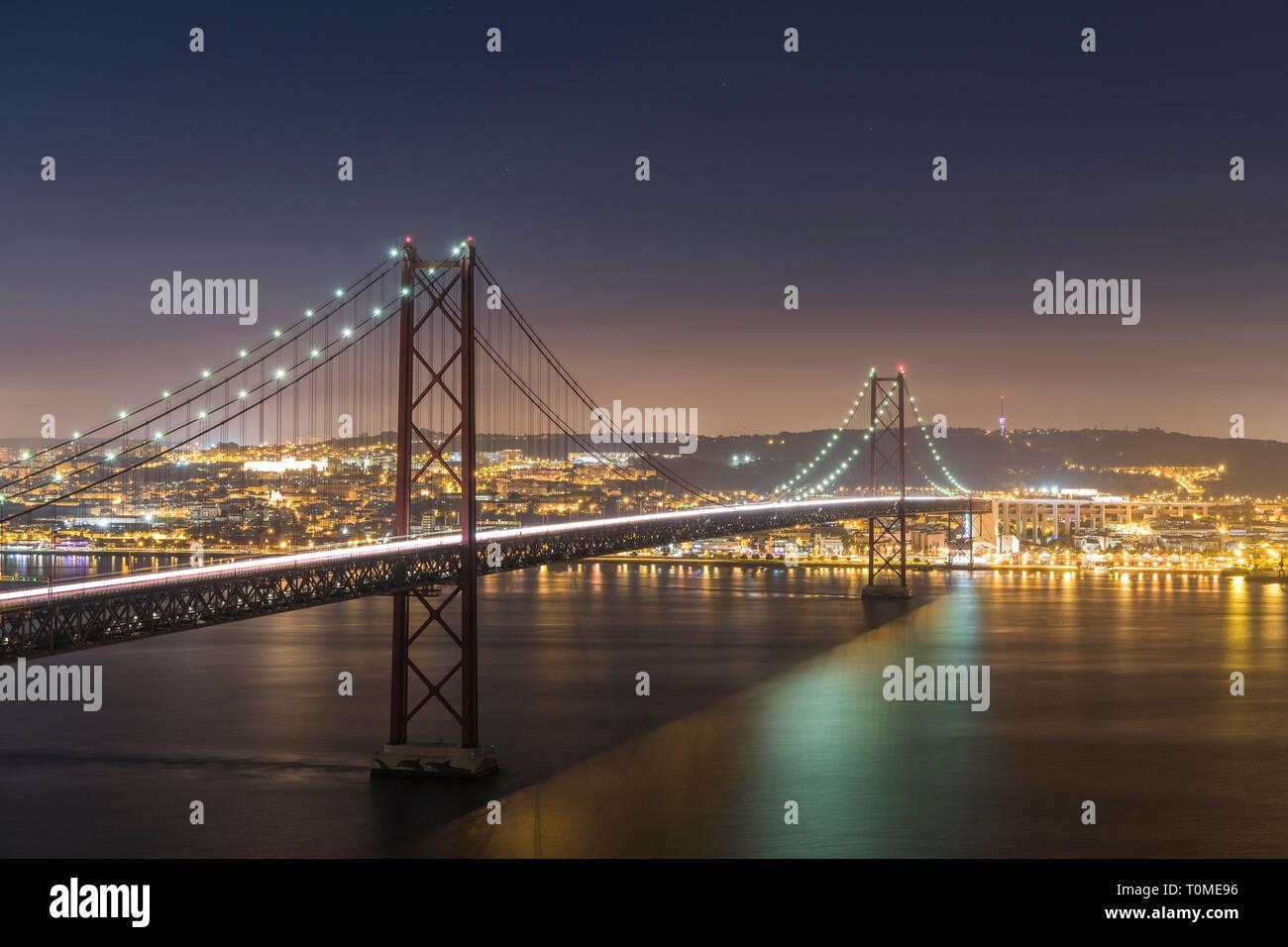 Night shot of Ponte 25 de Abril (bridge) and Lisbon, Portugal Stock Photo
