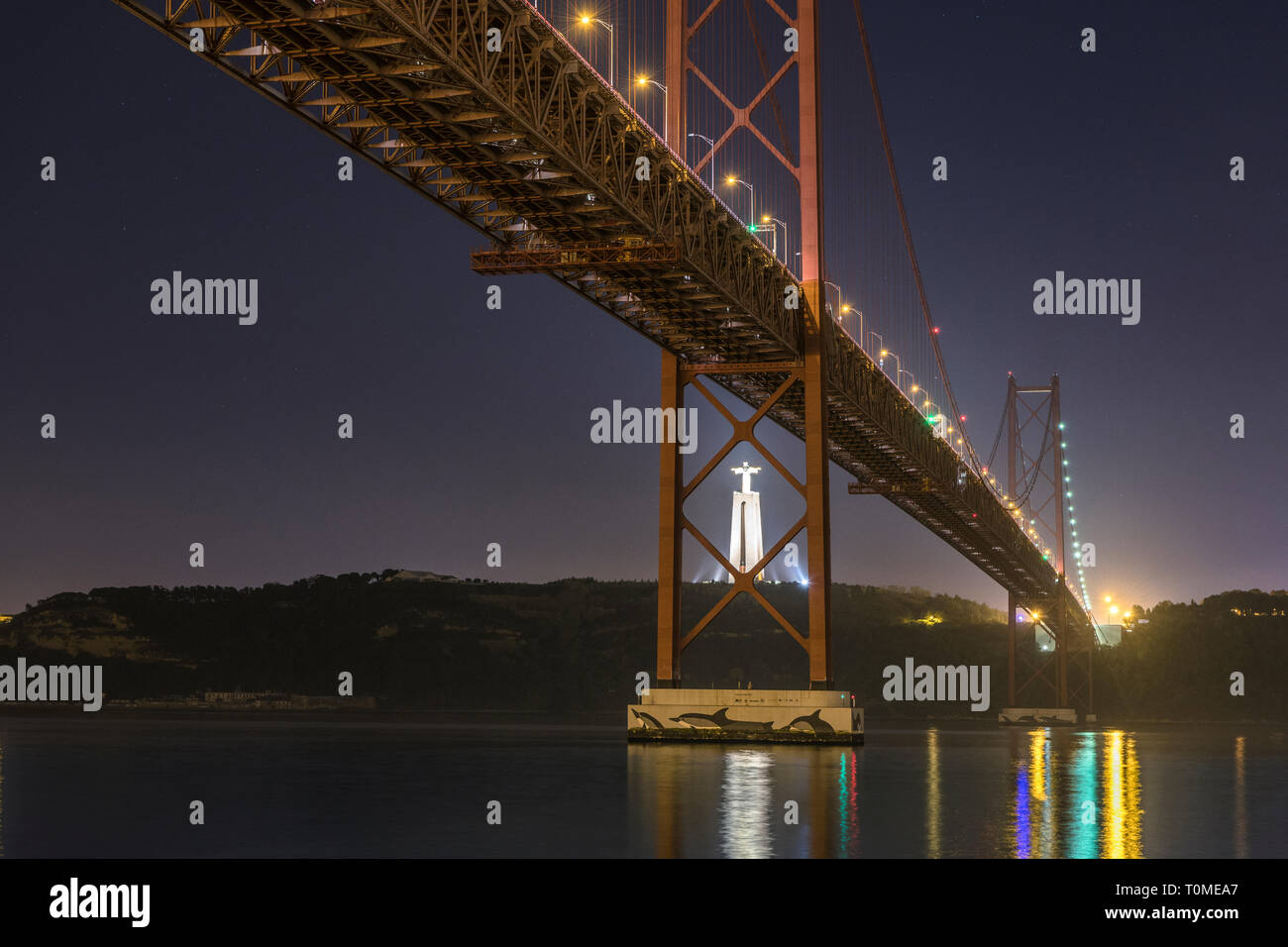 Night shot of Ponte 25 de Abril (bridge) and Cristo Rei (Christ statue in Almada), Lisbon, Portugal Stock Photo