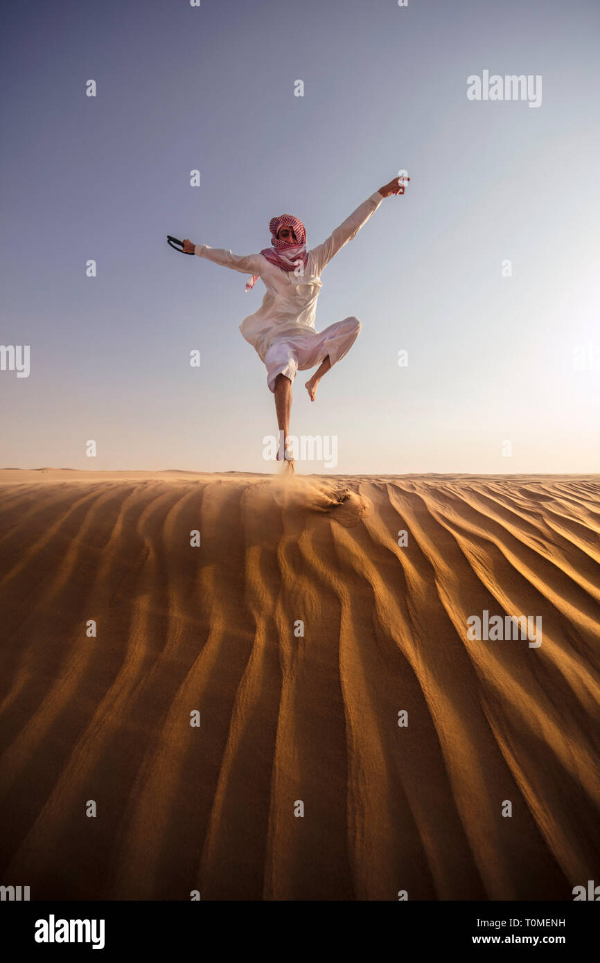 A Saudi man is jumping in desert, Saudi Arabia Stock Photo