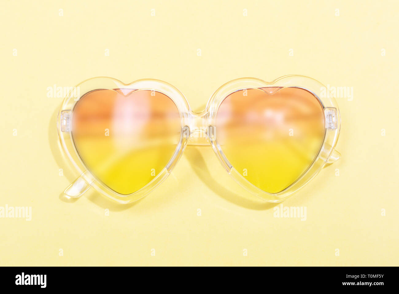 e4eb4ef20c34 Heart shaped sunglasses with gradient lenses. Pastel yellow background