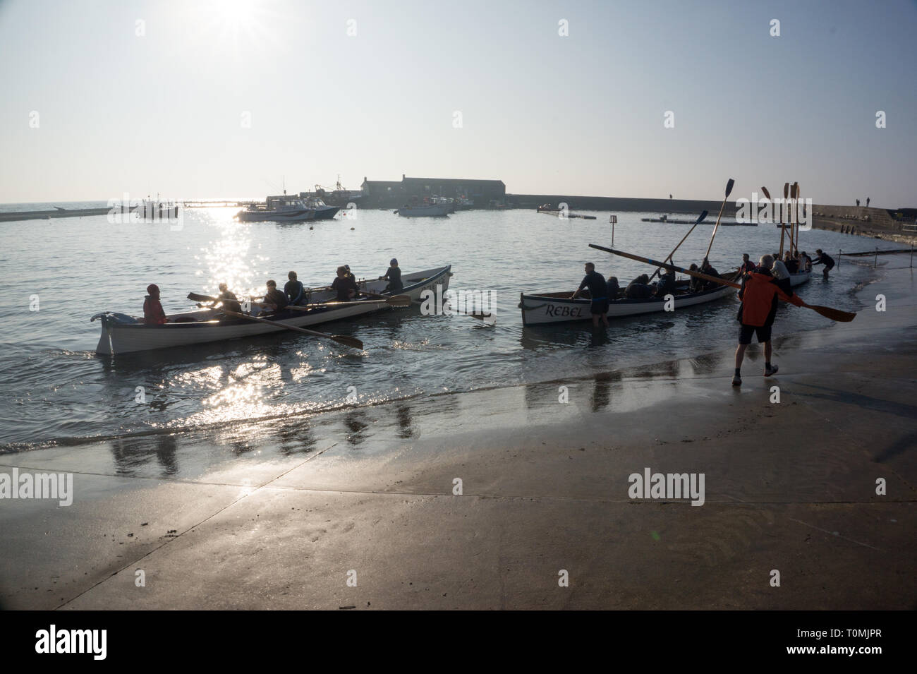 The Lyme Regis Gig club members setting out to sea from the Cobb, Lyme Bay, Dorset England UK - Stock Image