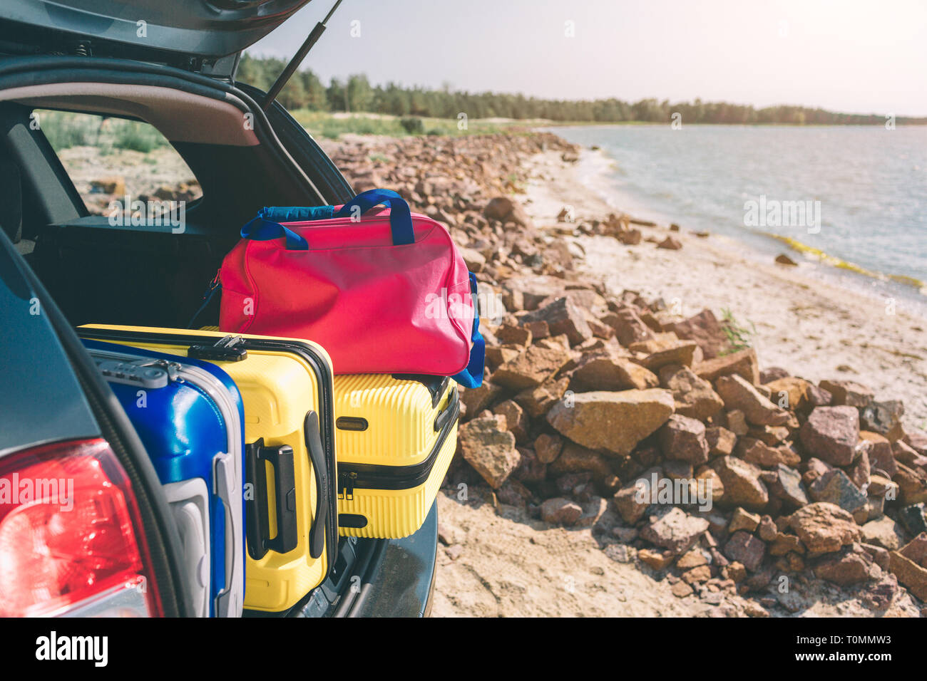 Suitcases and bags in trunk of car ready to depart for holidays. Moving boxes and suitcases in trunk of car, outdoors. trip, travel, sea. car on the b - Stock Image