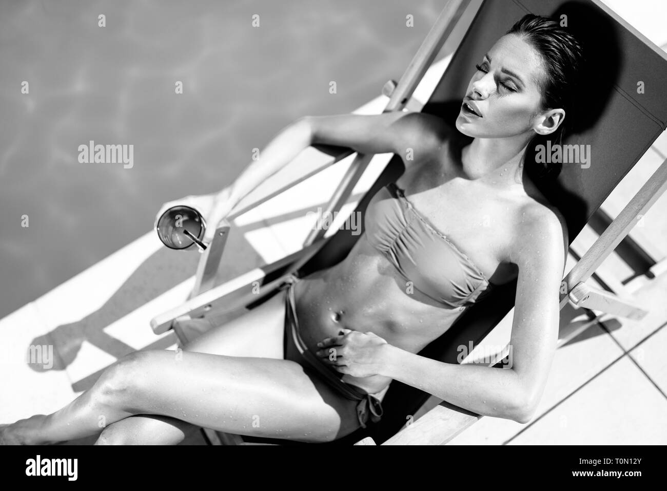 Beautiful woman drinking cocktail and sunbathing at pool - Stock Image