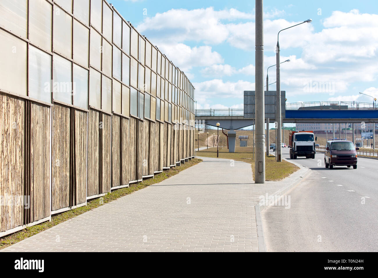Sound absorbing panels along freeway in city. Concept of protecting residential buildings from noise pollution using sound insulating panels. - Stock Image